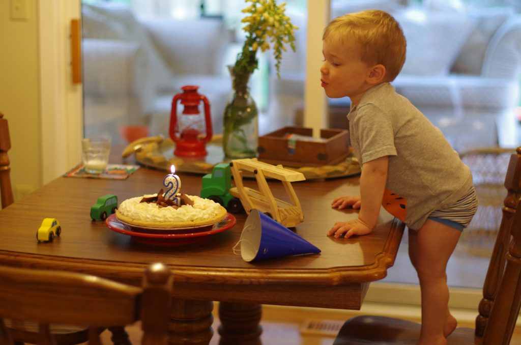 Family with Tippin's pie for 2nd Birthday - blowing out candle
